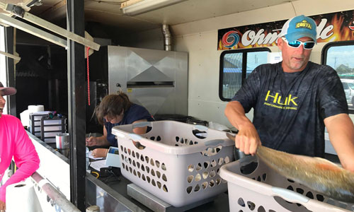 Cpt. C.R. Maher weighing in contestants redfish at a fishing tournament - Weighmaster